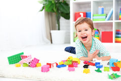 Happy child laughing and playing with toys constructor Royalty Free Stock Photos