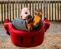 Happy child laughing while swinging royalty free stock photography