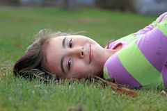 Happy child laying in grass. Royalty Free Stock Photography
