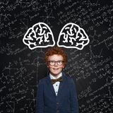 Happy child learning science. Redhead kid on background with science formulas royalty free stock photos