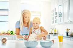 Happy child learning to bake with her mother Royalty Free Stock Photos