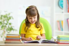 Happy child learning to read in nursery. Happy child girl learning to read in nursery Stock Image