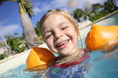 Happy child learning to swim in a swimming pool Royalty Free Stock Photography