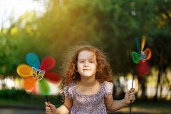 Happy child leisure in summer outdoor. Laughing girl holding a rainbow pinwheel toys Royalty Free Stock Image