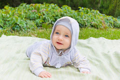 Happy child lies on the green grass Stock Images