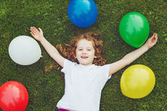 Happy child lies on green grass with rainbow balloons at summer Stock Image