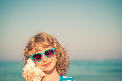 Happy child listen seashell on the beach Stock Photography
