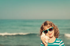 Happy child listen seashell on the beach Royalty Free Stock Photo
