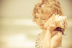 Happy Child Listen To Seashell At The Beach Stock Photos