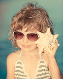 Happy child listen to seashell at the beach Royalty Free Stock Photography