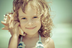 Happy child listen to seashell at the beach. Summer vacations concept Royalty Free Stock Images