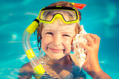 Happy child listen to seashell at the beach Stock Images