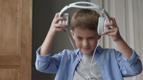 Happy child listening music or beautiful smiling boy with headphones. Melody playing for smiling carefree boy in domestic interior. Have kind feelings of life