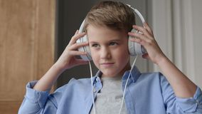 Happy child listening music or beautiful smiling boy with headphones stock footage