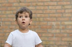 Happy child little boy in white t-shirt expresses delight at a blank empty brick wall. stock photography