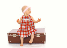 Happy child little girl in dress sitting on the suitcase playing Royalty Free Stock Images