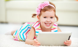 Happy child little girl playing in tablet computer Stock Photos