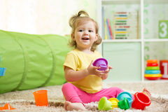 Happy child little girl playing with toys indoors Stock Photos