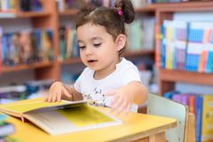 Happy child little girl reading a book. royalty free stock photos