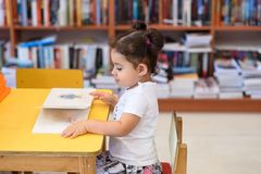 Happy child little girl reading a book. stock images