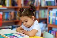 Happy child little girl reading a book. stock image