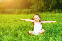 Happy child little girl spread his arms in white dress lying on. Happy child little girl spread his arms in a white dress lying on the grass Summer Stock Image