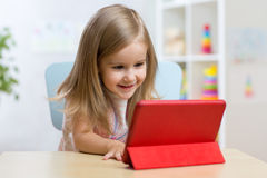 Happy child little girl using tablet computer Royalty Free Stock Image