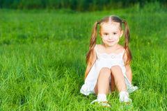 Happy child little girl in  white dress lying on grass Summer Stock Photos