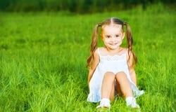 Happy child little girl in white dress lying on grass Summer stock photos
