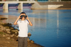 Happy child looking in nautical binoculars against blue water background. Kid having fun on nature. Summer sea dream and imagination. Adventure and travel stock image