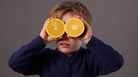 Happy child looking through oranges for fresh vision or health. Happy beautiful young child looking through two oranges as eyeglasses for a fresh exciting vision stock video
