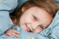 Happy child lying in bed Royalty Free Stock Photos