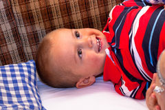 Happy child lying in the bed Stock Images