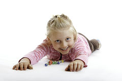 Happy Child is lying on the floor with marbles. On white background Stock Images