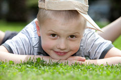 Happy child lying on the grass. Portrait of a happy little boy lying on the grass Royalty Free Stock Photo
