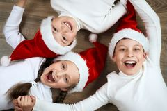 Free Happy Child Lying Together On Wooden Background, Dressed In Christmas Santa Hat And Having Fun, Winter Holiday Concept Stock Image - 102654471