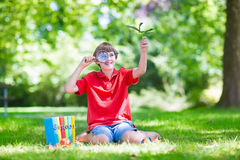 Happy child with magnifying glass Stock Photos