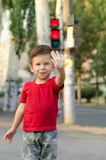 Happy child making a stop sign. With his hand while standing at the crossroads Royalty Free Stock Photo
