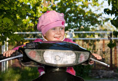 Happy child on the moped Royalty Free Stock Photo