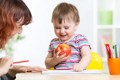 Happy child and mother draw with colorful pencils Royalty Free Stock Photos