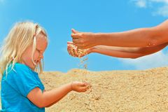 Happy child with mother on heap of rice grains crop. Royalty Free Stock Photos