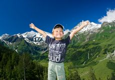 Happy child in a mountain scenery. Portrait of a happy child with Alps in the background Royalty Free Stock Image