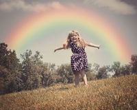 Happy Child in Nature Field with Rainbow. A little child is dancing in an open grass field with wind blowing in her hair and a rainbow in the background for a royalty free stock image