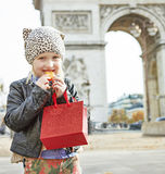 Happy child near Arc de Triomphe in Paris eating French macaroon. Stylish autumn in Paris. happy modern child with red present bag near Arc de Triomphe in Paris Stock Photos
