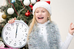Happy child near Christmas trees. Happy little girl in Santa hat is happy Christmas Royalty Free Stock Image