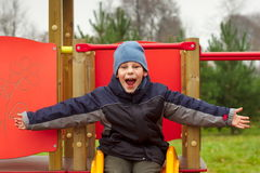 Happy child open arms screaming of joy playground. Happy child with open arms screaming of joy in playground and trees background Stock Photos