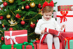 Happy child opens Christmas gifts near  tree Royalty Free Stock Image