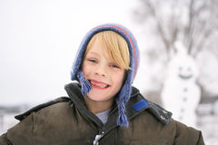Happy Child Outside playing in the Snow after Building Snowman Stock Image