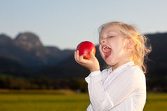 Happy child outside with red apple Royalty Free Stock Photography