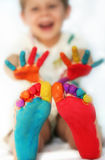Happy child with painted feet and hands. Five year old boy with feet and hands painted in colorful paints ready for hand prints. Very shallow DOF with focus on Royalty Free Stock Photo